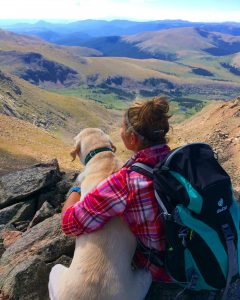 girl and dog backpacking with mountain vista